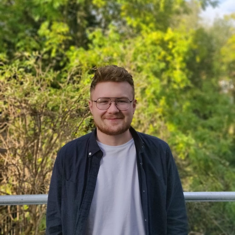 Tom Shuttleworth, Web and Marketing, stood in front of some trees