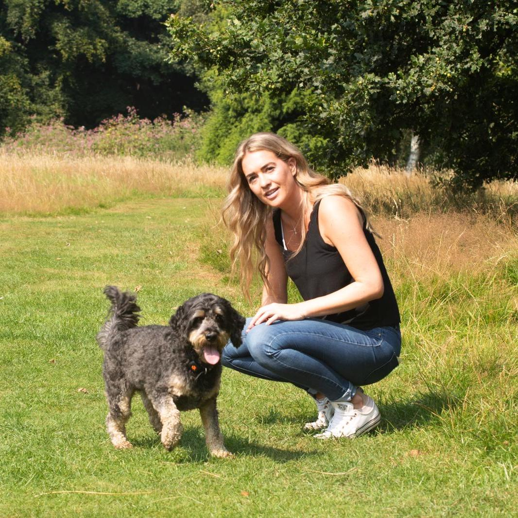 Our Founder, Becky, and her Cockapoodle Buddy, stood in a park in the sun
