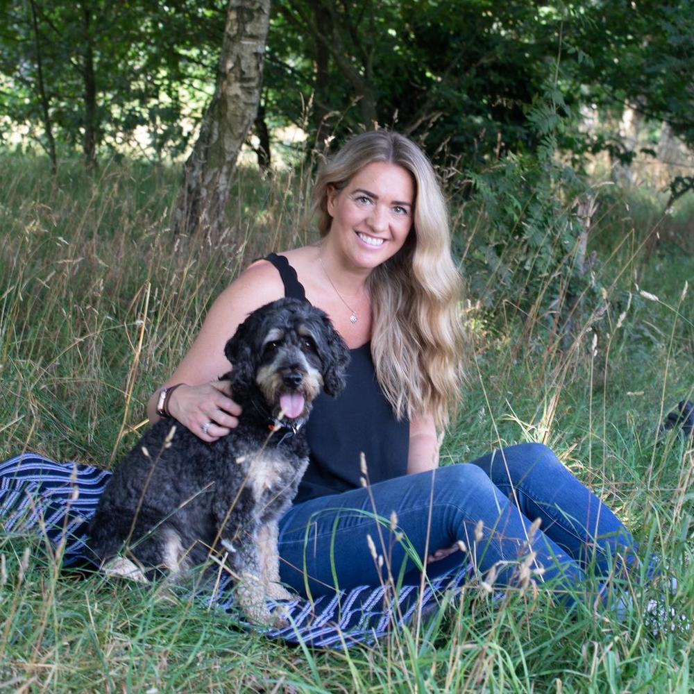 Our Founder, Becky, and her Cockapoodle Buddy, sat in a field, under a tree