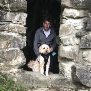 David, our CFO, and his dog Whiskey, an Australian Labradoodle, stood by a stone wall