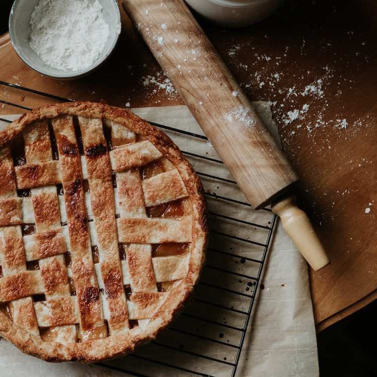 Dog Pie - A cooked pie on a cloth on a table, next to a rolling pin and a small pot containing flour