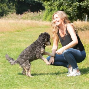The founder of our dog owner community, Becky, and her Cockapoodle Buddy, stood in a park in the sun